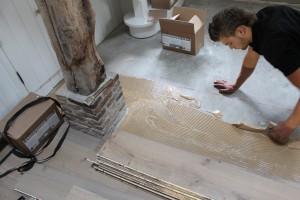 Met precisie worden vloeren gelegd, op de foto wordt een houten vloer volledig verlijmd aan de ondergrond in een woning in Lelystad.