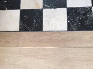 Tegels kunnen aansluiten op de houtenvloer door middel van flexibele kit. Op de foto ziet u een voorbeeld uit Den Haag.